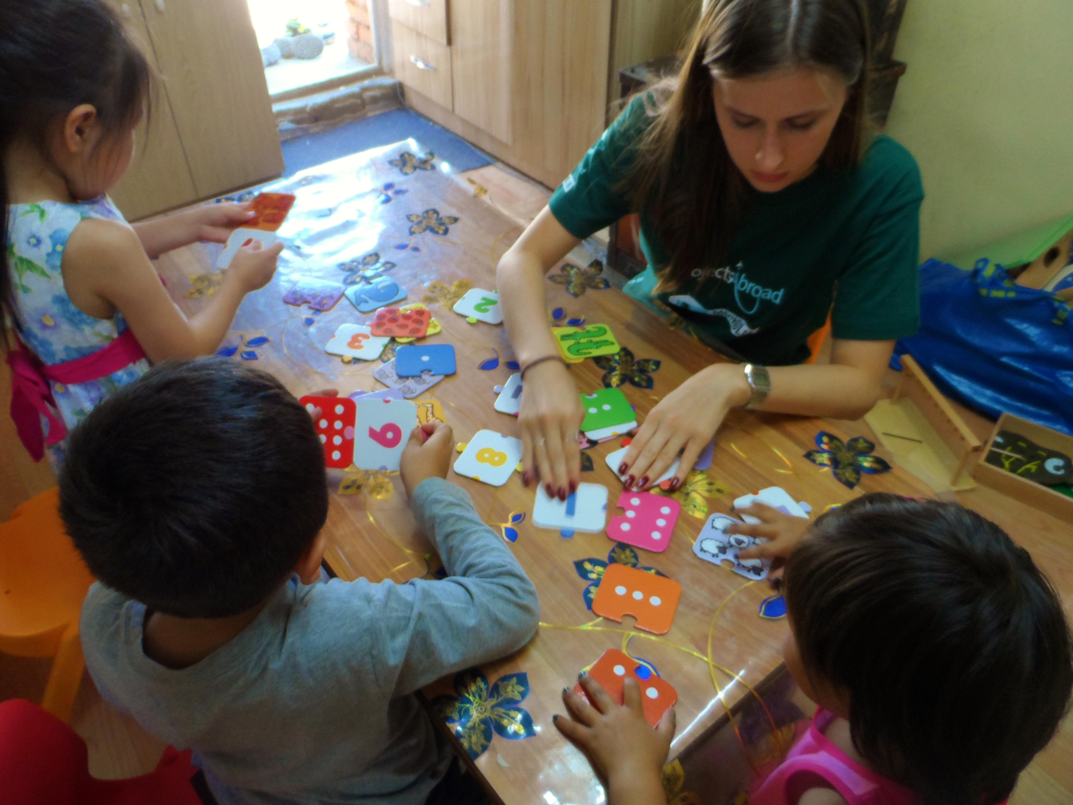 Projects Abroad volunteer working with children in Mongolia helps a group of children with mathematic skills at a care centre.